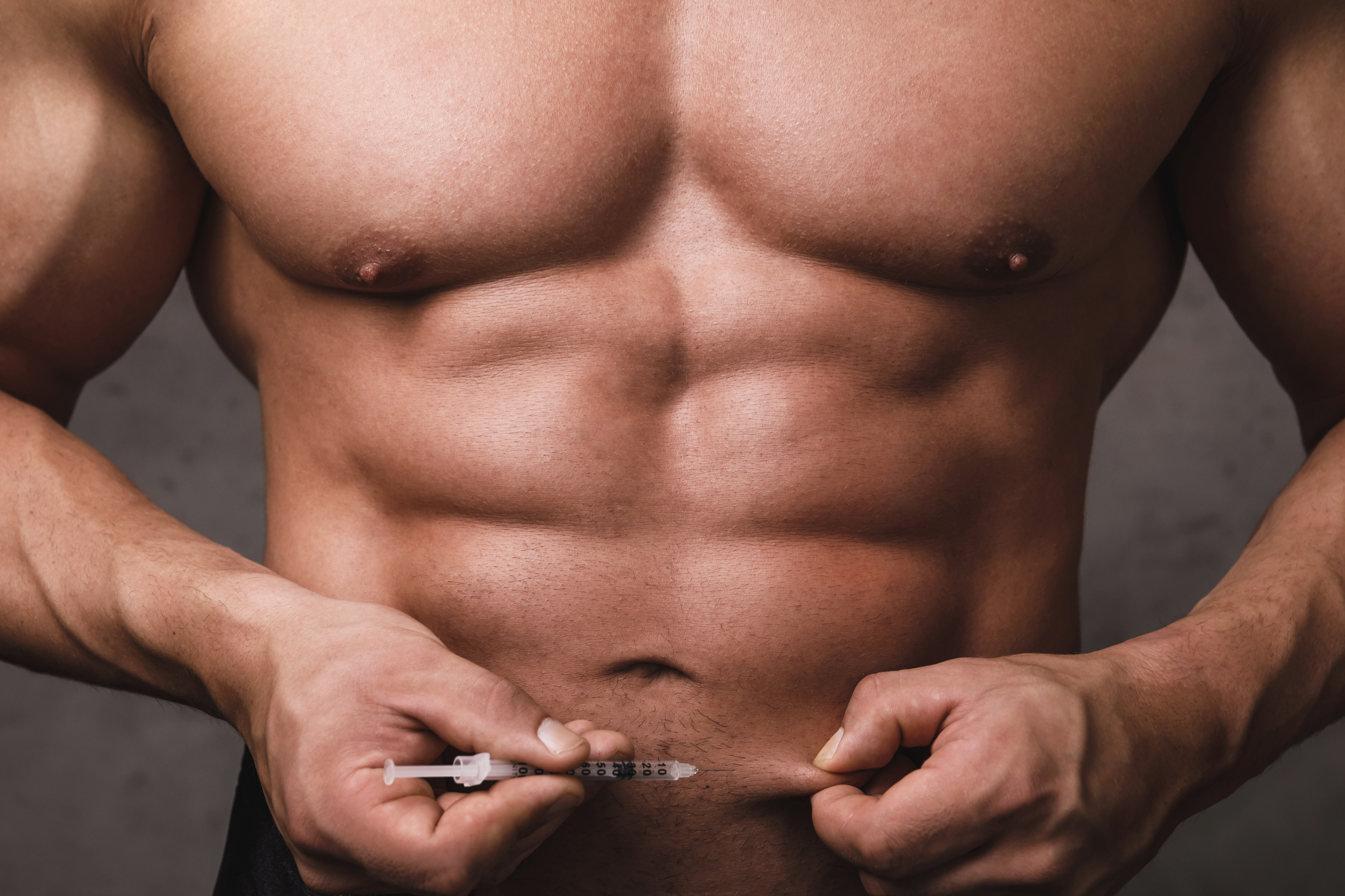 Muscular bodybuilder is prepared to make subcutaneous injection in the belly